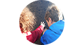Deux enfants touchent une plaque commémorative du Mont-Valérien.
